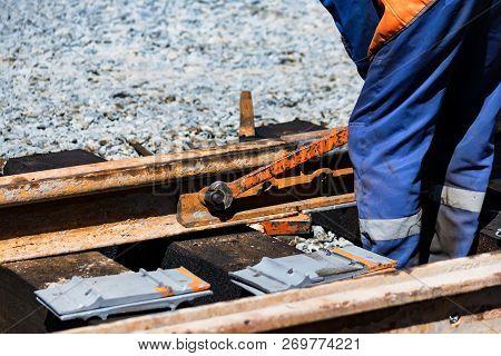 Worker Tightens The Skrew In Railway Or Tram Tracks