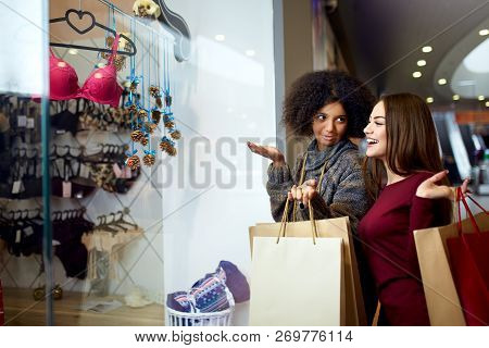 Two Happy Multiethnic Young Mixed Race Woman Shopping For Lingerie Near Clothing Boutique Shop Windo