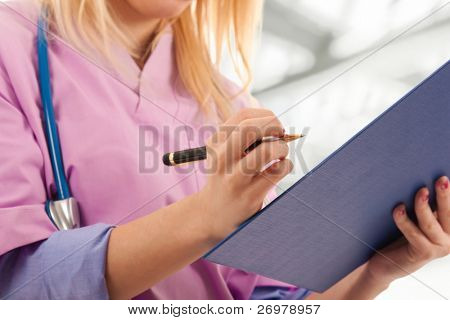 Young nurse writing medical records