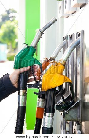 Man holding a gasoline nozzle in his hand