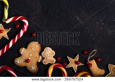 New Year And Christmas Background. Christmas Candy Cane  Gingerbread On Black Background. New Year A