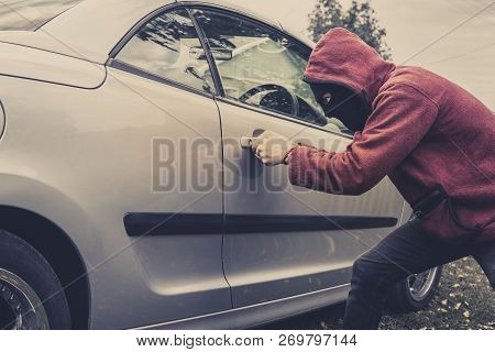 Side View Of Car Being Forced By A Man In Hoodie And Mask. Thief Tries To Steal Vehicle From A Parki