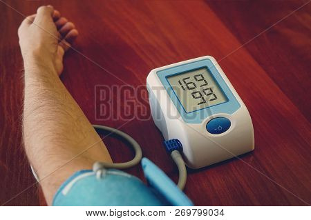 Blood Pressure Digital Pulse Monitor. Man Measuring Her Blood Pressure And Hearth Rate. Health. Hype