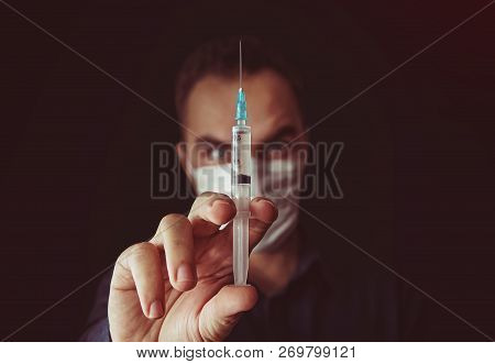 Out of focus doctor with syringe in a dark background. doctor keeps talking in the hands of a syringe with a medicine. Sultry doctor. Unskilled specialist. Amateur doctor. batty, demented, deranged, poster