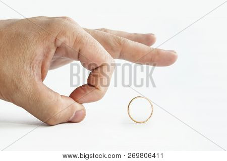 Close Up Of Persons Hand Pushing Away Wedding Golden Ring Isolated On White. Man Makes Finger Kick O