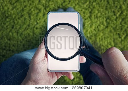 Top-down View To Sitting Man With Blank Smartphone And Magnifying Glass Above Its Screen. Man Holds