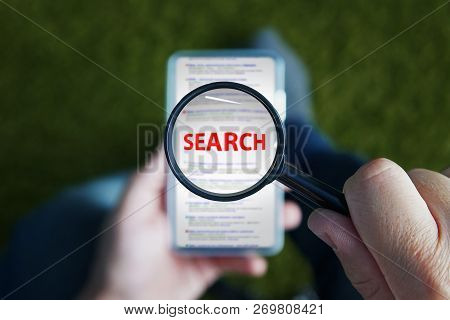 Close Up Of A Man Sitting And Looking Through Magnifying Glass With Red Written Word Search On The L
