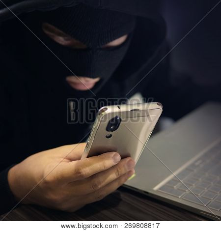 Male Hacker In A Black Mask Uses Smartphone And Laptop. A Fraudster Commits Cyber Crime. Fraudulent