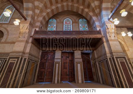 Cairo, Egypt - November 3 2018: Marble Decorated Wall With Wooden Doors, Huge Arches And Stained Gla