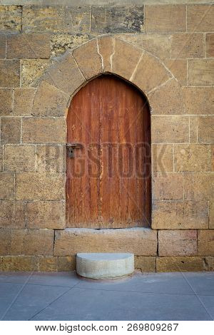 Old Wooden Door And Window Framed By Arched Bricks Stone Wall At The Courtyard Of Al Razzaz Historic
