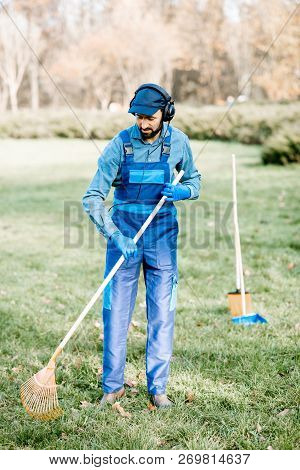 Professional male sweeper or gardener in uniform listening to the music with headphones while cleaning the garden poster