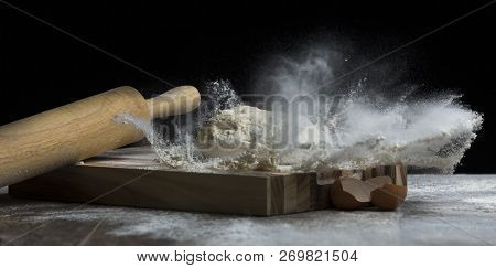 Studio Photo Of A Ball Of Bread Dough Falling On Flour With Roller And Egg Shells