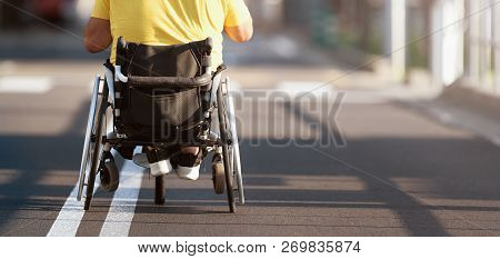 Disabled Man In Wheelchair On Road, Man In The Street In A Wheelchair