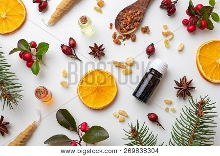 Bottles Of Essential Oil On A White Christmas Background With Frankincense, Myrrh, Wintergreen And V