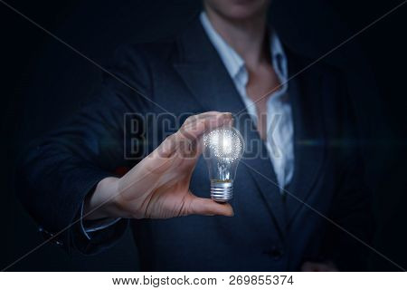 A Businesswoman Is Holding A Lightbulb With A Digital Brain Model Inside. The Concept Is The Success