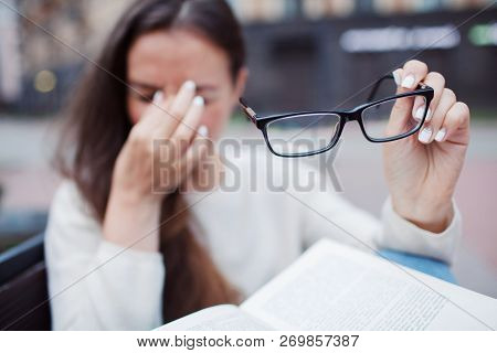 Closeup Portrait Of Attractive Female With Eyeglasses In Hand. Poor Young Girl Has Issues With Visio