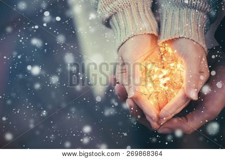 Close View Of A Couple Holding Warm Christmas Lights Snow Falling Vintage Toning