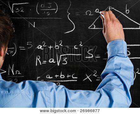 Man writing math formulas on a blackboard