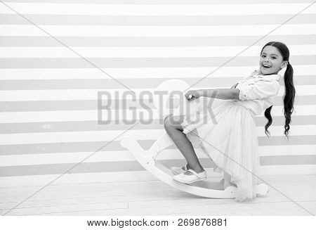 Have Fun. Girl Child Rides White Rocking Horse On Striped Background. Child Girl Happy Face With Lon
