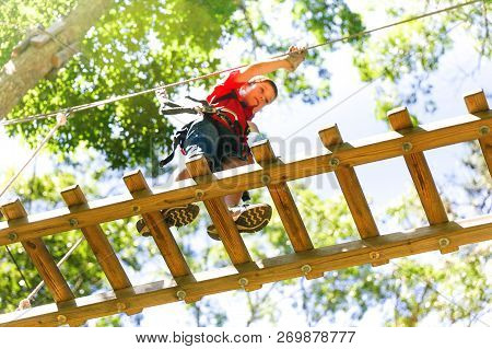 Brave Boy Walks On The Wooden Ladder In A Rope Park. The Child On The Zip Line.