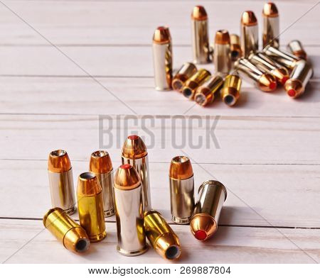 Two sets of 40 caliber bullets and 44 special bullets on a white wooden background. The set in the background is slightly blurred, spotlighting the one in the foreground poster