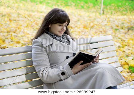Picture of a girl who reads the book in the park on a bench