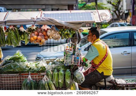Bangkok, Thailand - November 2018: Salesman Is Riding On His Bike With Vegetables And Fruits In Bang