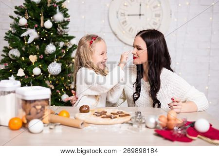 Portrait Of Happy Woman And Her Daughter Cooking Christmas Cookies In Kitchen With Christmas Tree