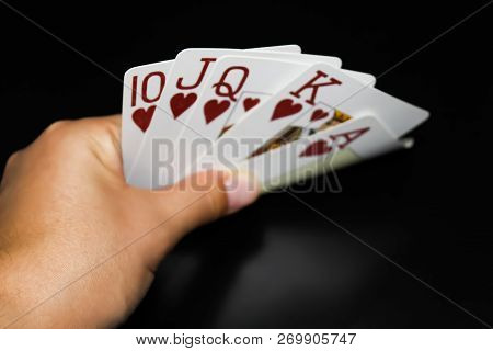 Combination of cards in poker royal flush with a hand on a black background poster