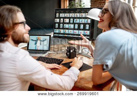 Young Couple Of Photographers Working With Womans Portraits At The Working Place With Two Computers