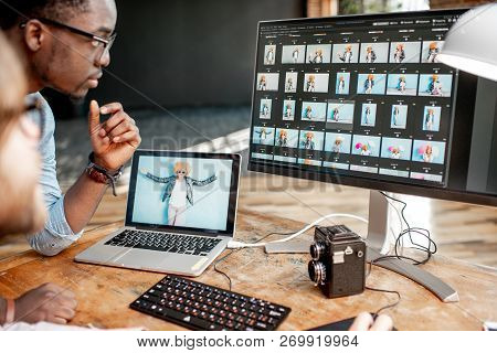Two Male Photographers Choosing Womans Portraits At The Working Place With Two Computers In The Stud