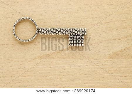 Silver Key On Wooden Surface With Copy Space