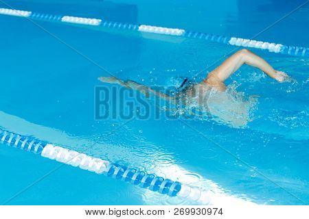 Photo of athlete man in blue cap swimming under water in swimming pool