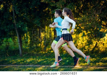 Photo of young athlete woman and man running in park