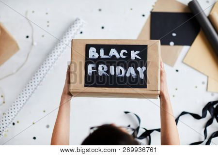 Directly above view of unrecognizable woman holding gift box with painted  lettering Black Friday over table with wrapping paper