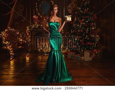 Magical Christmas night. Beautiful woman in evening dress with a gift box celebrates Christmas in luxurious apartments decorated christmas lights.