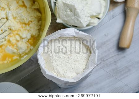 Cooking Process Of Homebaked Cottage Cheese Pie. Raw Ingredients In Bowl And Flour. Table With Kitch