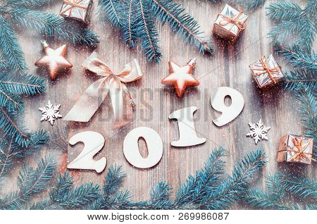 New Year 2019 background with 2019 figures, Christmas toys, blue fir tree branches and snowflakes. New Year 2019 festive composition