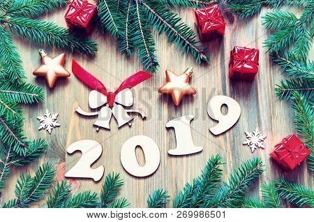 New Year 2019 background with 2019 figures, Christmas toys, green fir tree branches and snowflakes. New Year 2019 holiday still life in vintage tones