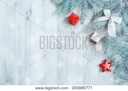 Christmas background. Christmas toys, blue fir tree branches on the wooden background. Christmas still life with space for text