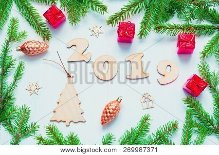 New Year 2019 background with 2019 figures, Christmas toys, green fir tree branches. Flat lay, top view, New Year 2019 festive still life