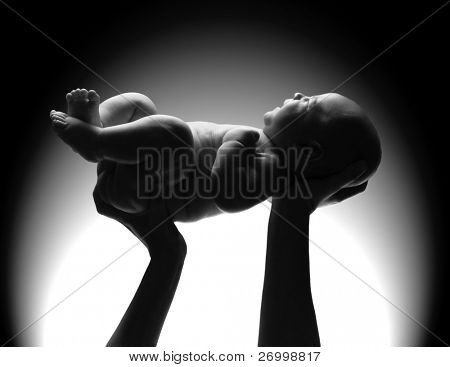 Mother's hands holding a newborn baby.
