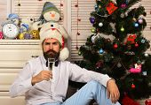 Guy sits near Christmas tree and bureau with toys poster