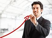 Portrait of a smiling businessman drawing a rising arrow, representing business growth poster
