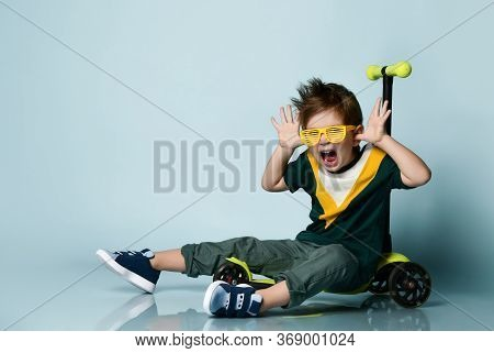 Little Brunet Kid In Colorful T-shirt, Yellow Sunglasses, Gray Jeans And Sneakers. Screaming, Making