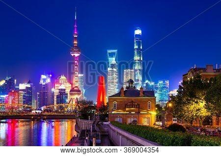 Illuminated Shanghai Pudong Skyline With Historical Waibaidu Bridge, China During Twilight Sunset