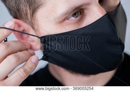 Man Puts On A Face Mask. Black Stylish Face Mask During A Pandemic Virus Crown. Handmade Cotton Face