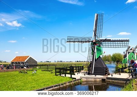 Typical Iconic Landscape In The Netherlands, Europe. Traditional Windmills With A River In Zaanse Sc