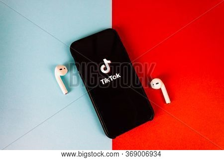 Iphone With Tiktok App Logo On The Screen. Red-blue Background.