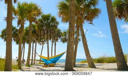 Romantic Couple Relaxing In Tropical Hammock. Young Couple In Love Relaxing In A Hammock By The Beac